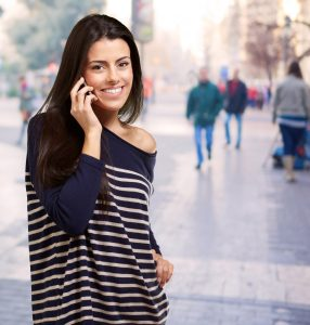 portrait of young woman talking on mobile at street